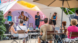 Band on stage under covered tent structure at cultural event