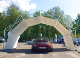 Purple car under protected tent structure at car event
