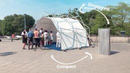 A deployed pop up structure with people and the closed structure for a size comparison next to it.