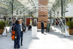 People at networking event under white design structure