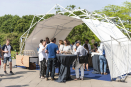A scissor structure tent with people at a team event.