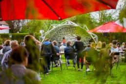Een festival in een tuin met een innovatieve overkapping voor het podium
