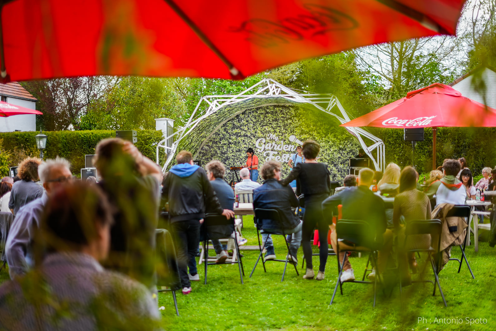 A festival with people and a stage in a garden