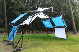 Pop up tent structure with blue and white panels for brand activation