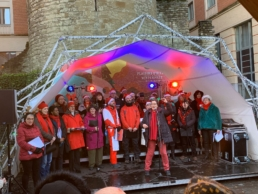 Choir under sheltered tent structure with light effects