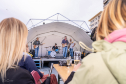 Band on stage under covered tent structure