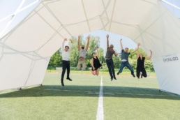 Teammembers jumping under scissor structure tent