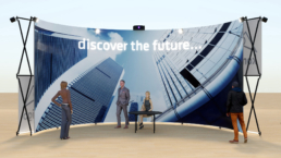 People in front of Curved structure with screen as exhibition stand