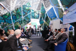 People in a room at conference in Ondo scissor structure with blue panels