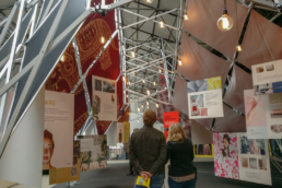 People looking at scissor strucutre exhibition booth.