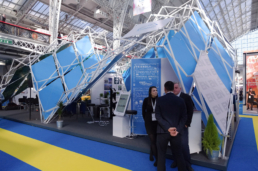 People in front of open and transparent stand at exhibition