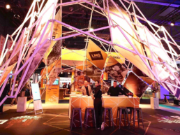 People under scissor structure as stand booth at exhibition for brand activation